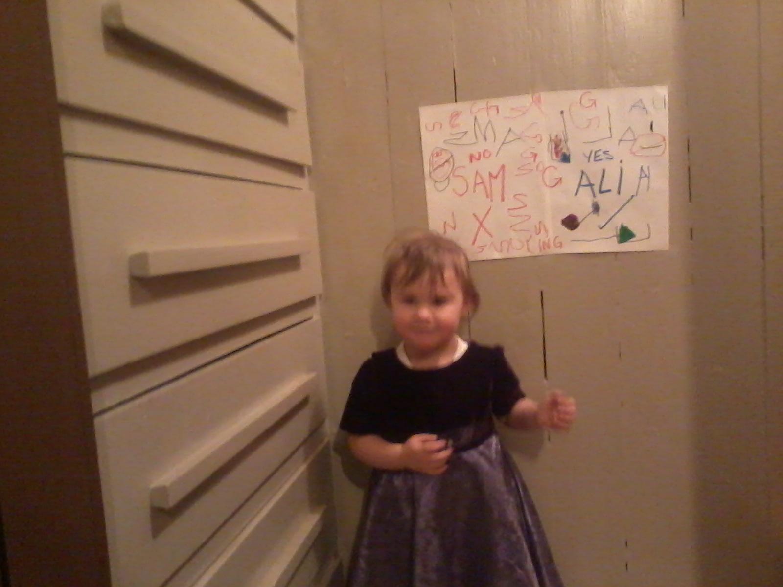 Sam/Sammi standing near Ali's wall drawing.