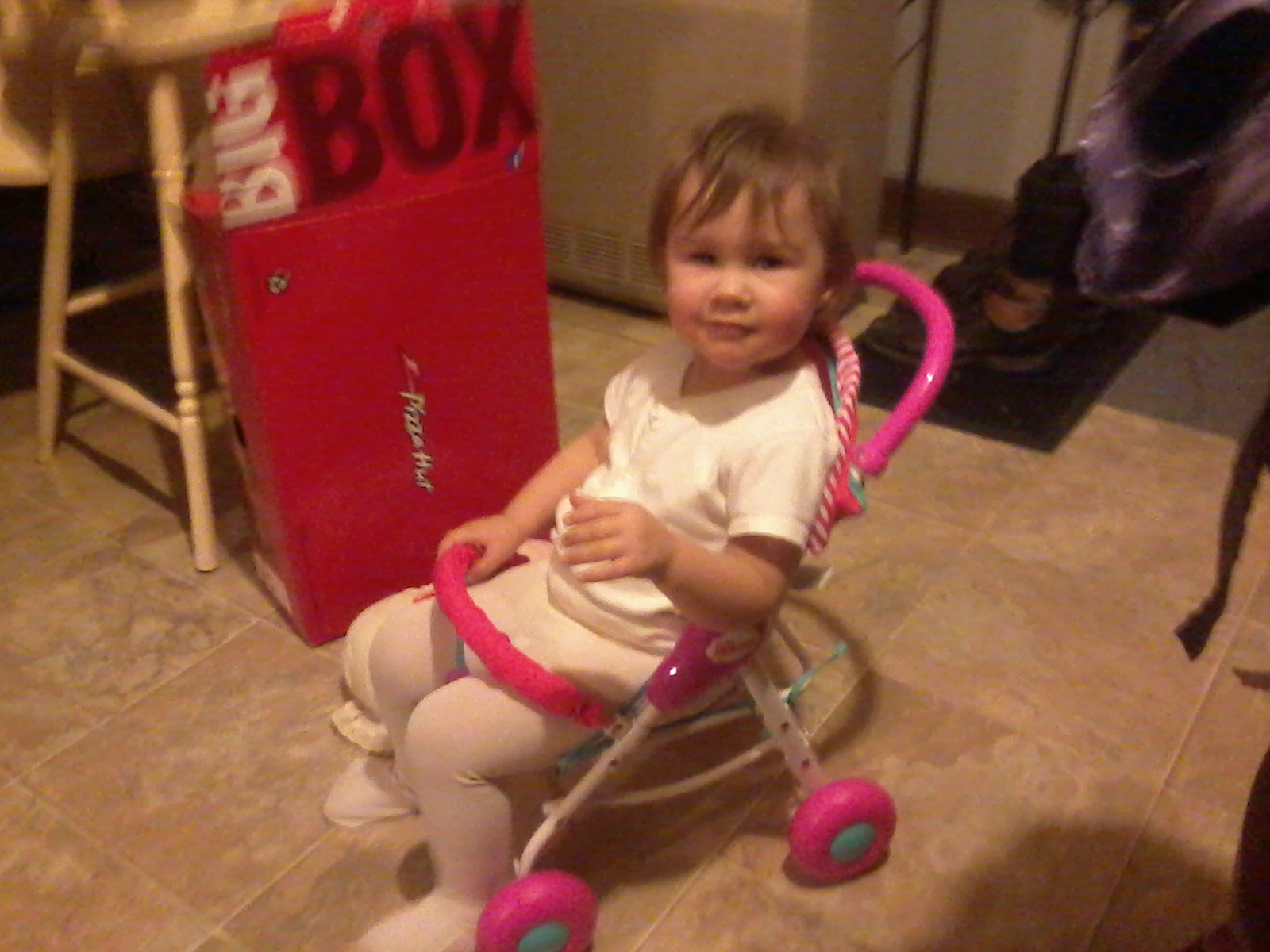 Sam, sitting in her new doll stroller - she wasn't pushing it; she HAD to sit in it!
