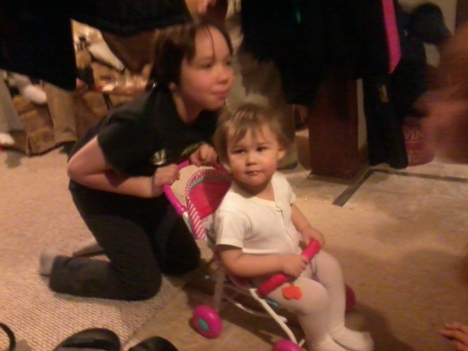 Caleb pushing Sammi in her new doll stroller.