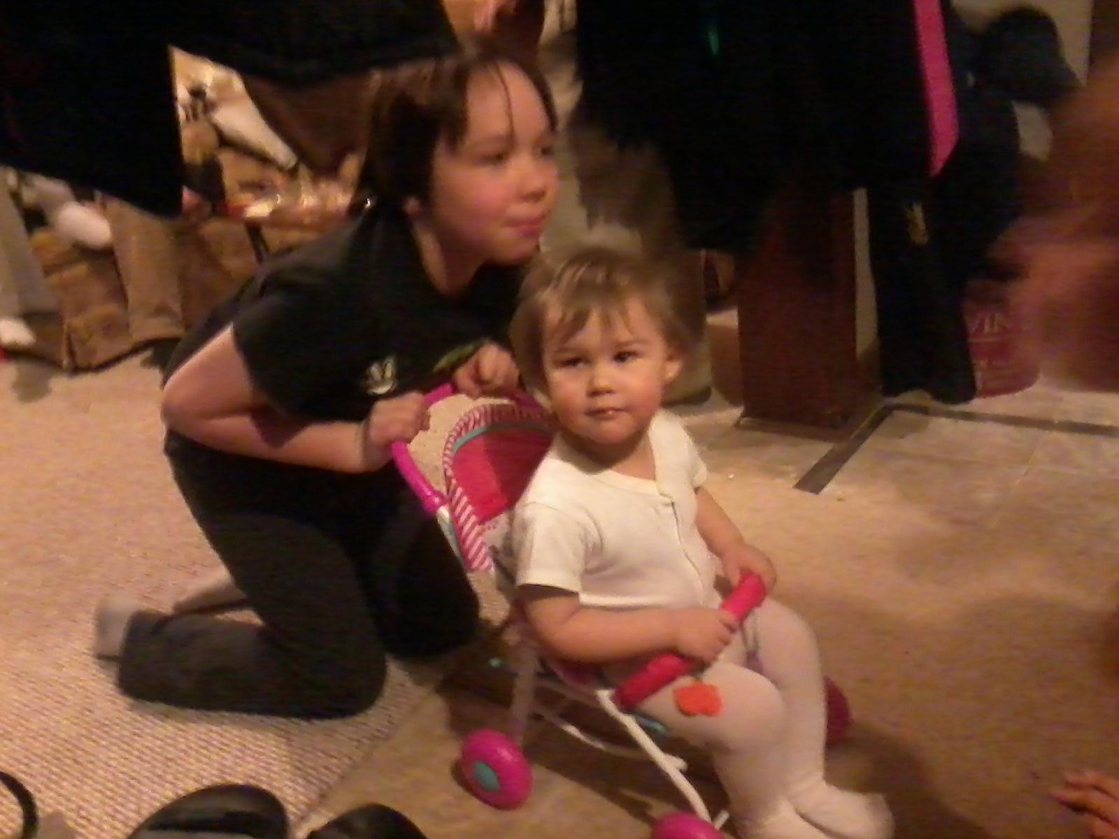 Caleb pushing Sammi in her new doll stroller.