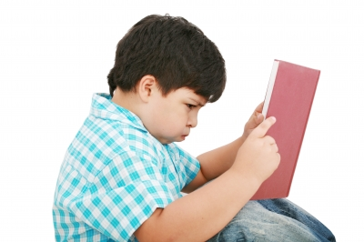 Young Boy reading a book, and struggling to do so