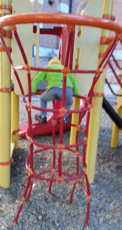 Sam climbing the net on the playground equipment at the school across from RMH